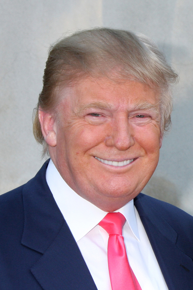 A photo of Donald Trump dressed in a suit. He is smiling.