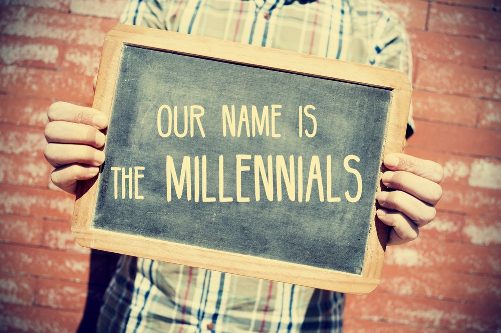 "A photo of a young man holding a chalk board sign that reads, ""Our name is the millennials."""