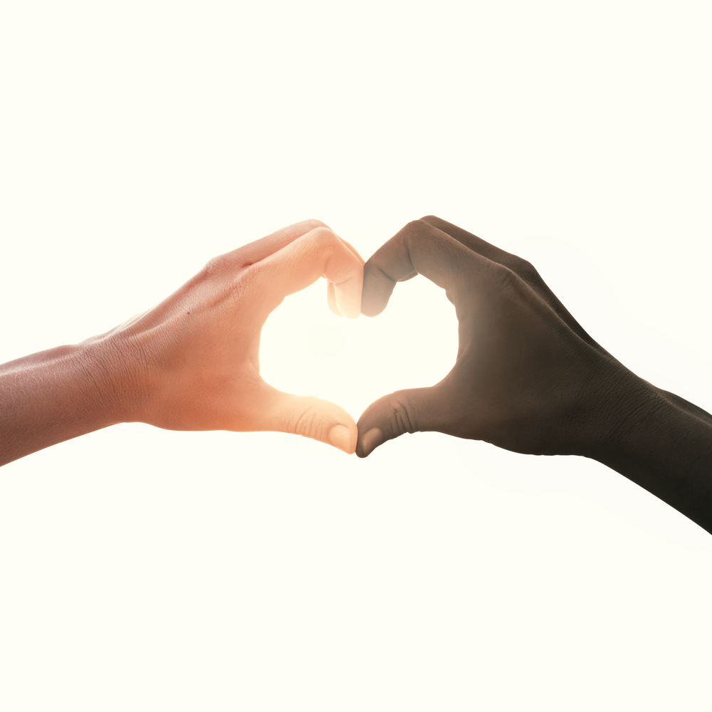 A white hand and a black hand come together to form a heart.