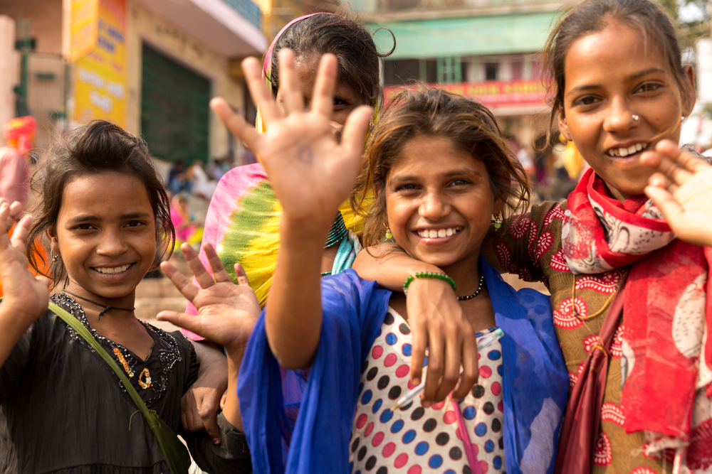 Four young Indian girls smile for the camera.