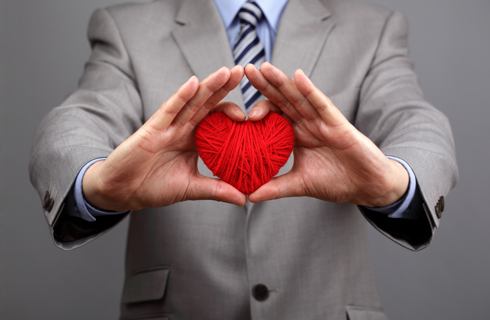 Man in business suit hold hands around red heart