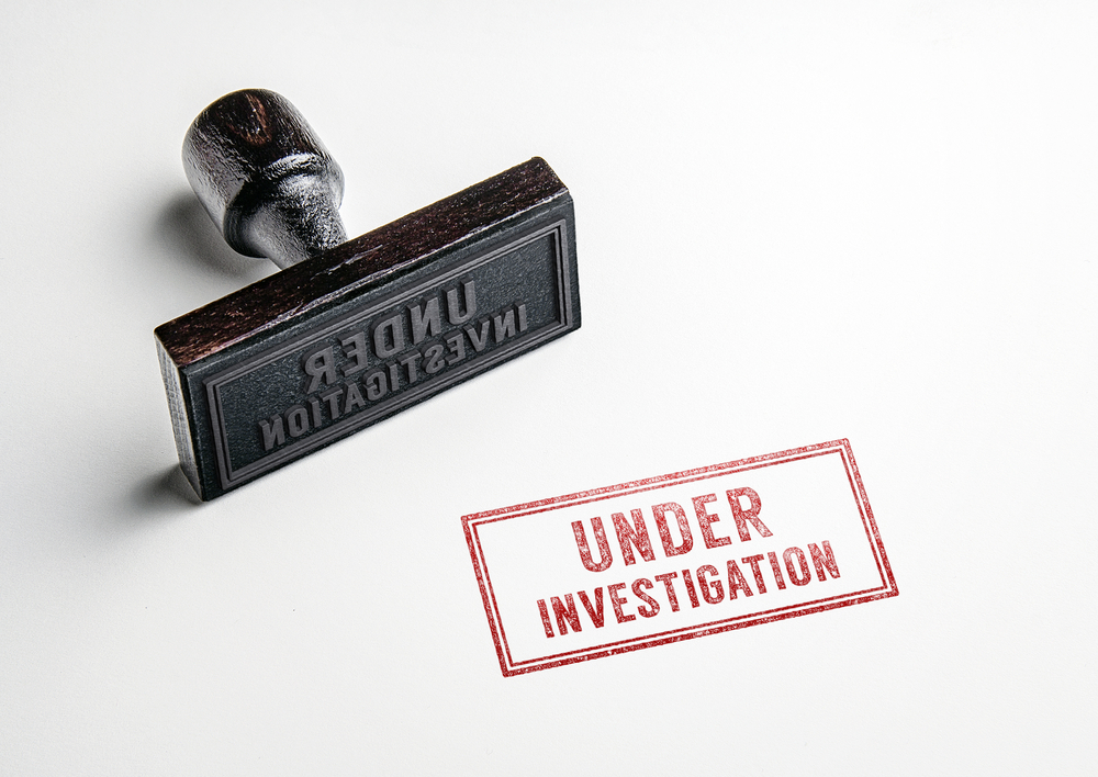 """A red stamp that reads, """"under investigation."""""""