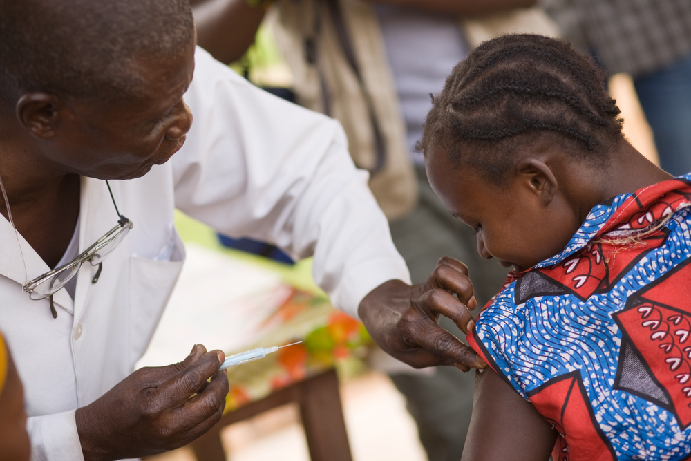 A photo of a medical professional in the Democratic Republic of Congo administering a vaccine to a child.