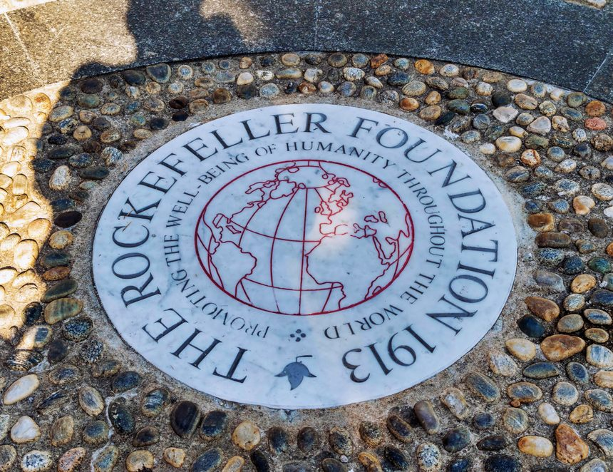 A stone monument engraved with the Rockefeller Foundation's emblem.